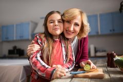 Grandmother and cute granddaughter cooking salad. Close up of happy grandmother and granddaughter posing on camera. Family concept Royalty Free Stock Photo