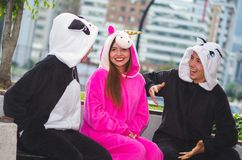 Close up of a happy group of friends having a fun conversation and wearing different costumes, one woman wearing a pink Royalty Free Stock Image