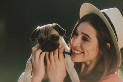 Lovely woman in hat is cute hugging her pet royalty free stock photography
