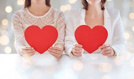 Close up of happy lesbian couple with red hearts Stock Images