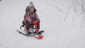Close up of happy little girl sitting on her red sleigh and sliding down from the hill. Small princess is spending her stock video