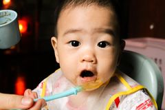 Close up of happy little seven months old son in see through plastic bib eating in chair for babies after mom made him eat avocad. O and banana mix.Happy baby`s stock image