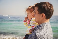 Close up of happy loving family, father and small daughter together near the ocean, young father is holging his kid in arms.  Royalty Free Stock Photo