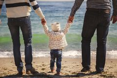 Close up of happy loving family with small kid in the middle, walking at beach together near the ocean, holding arms, happy lifest. Yle family concept Royalty Free Stock Image