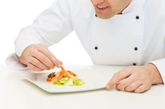 Close up of happy male chef cook decorating dish Stock Image