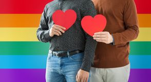 Close up of happy male couple holding red hearts. Gay pride, lgbt and homosexual concept - close up of happy male couple holding red hearts over rainbow colors Stock Image