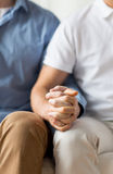 Close up of happy male gay couple holding hands. People, homosexuality, same-sex marriage, gay and love concept - close up of happy male gay couple holding hands Stock Photography