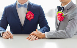 Close up of happy male gay couple holding hands. People, homosexuality, same-sex marriage and love concept - close up of happy married male gay couple in suits Stock Photos