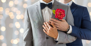 Close up of happy male gay couple. People, homosexuality, same-sex marriage and love concept - close up of happy married male gay couple in suits with Stock Photography
