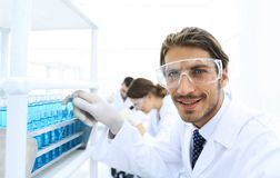 Close-up of a happy male scientist wearing safety glasses. Handsome doctor in gloves and mask holding a test tube, looking at the camera and smiling while Royalty Free Stock Images