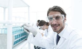 Close-up of a happy male scientist wearing safety glasses. Handsome doctor in gloves and mask holding a test tube, looking at the camera and smiling while Stock Photography