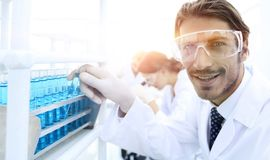 Close-up of a happy male scientist wearing safety glasses. Handsome doctor in gloves and mask holding a test tube, looking at the camera and smiling while Royalty Free Stock Photos