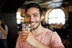 Close up of happy man drinking beer at bar or pub Stock Photo