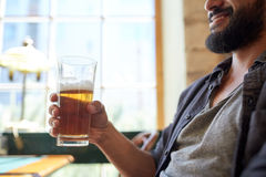 Close up of happy man drinking beer at bar or pub Royalty Free Stock Photos