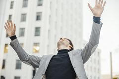 Close up of happy man smiling and raising his arms while going to or from work. royalty free stock photos