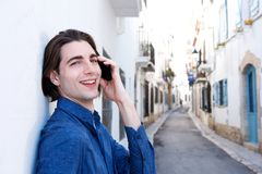 Close up happy man standing on city street talking on mobile phone Royalty Free Stock Photo