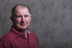 Close up of a happy mature man on a grey background stock photo