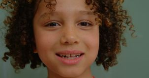 Close-up of happy mixed-race schoolgirl standing against chalkboard in classroom at school 4k. Close-up of happy mixed-race schoolgirl standing against stock video footage