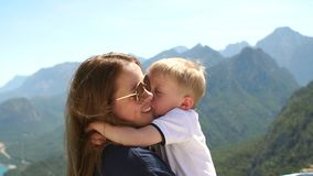 Mom with baby enjoy views of the mountains and the sea high in the mountains.
