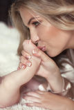 Close-up of happy Mother kissing Baby's feet her Newborn baby gi Royalty Free Stock Photography