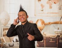 Close up of happy office punk worker wearing a suit with a crest, using his cellphone in the office in a blurred. Background Royalty Free Stock Photos