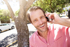 Close up happy older man standing outdoors with mobile phone Stock Photo