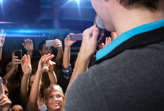 Close up of happy people at concert in night club Stock Images
