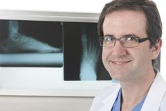 Podiatrist with his X-rays. Close up of a happy podiatrist in front of his lightbox with foot X-rays Royalty Free Stock Photos