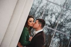 Close up of happy romantic attractive young couple kissing and hugging at the street.  royalty free stock images