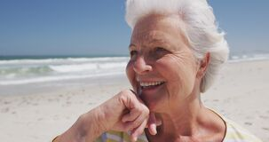 Close up of happy senior caucasian woman with hand on chin sitting on the beach enjoying the view