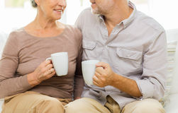 Close up of happy senior couple with cups at home Stock Photos