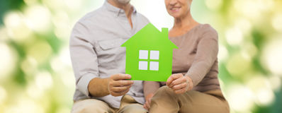 Close up of happy senior couple with green house Stock Images