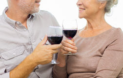Close up of happy senior couple with red wine. Family, holidays, drinks, age and people concept - close up of happy senior couple clinking glasses with red wine Stock Photos