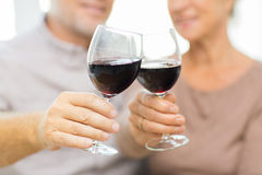 Close up of happy senior couple with red wine. Family, holidays, drinks, age and people concept - close up of happy senior couple clinking glasses with red wine Stock Photo