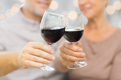 Close up of happy senior couple with red wine. Family, holidays, drinks, age and people concept - close up of happy senior couple clinking glasses with red wine Royalty Free Stock Photo