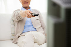 Close up of happy senior woman watching tv at home. Family, technology, television, age and people concept - close up of happy senior woman watching tv at home Stock Photography