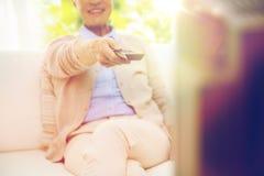 Close up of happy senior woman watching tv at home Royalty Free Stock Image