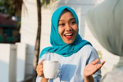 Close up happy shot two hijab women drinking tea in front of the house and smiling royalty free stock images