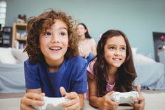 Close-up of happy siblings with controllers playing video game. On carpet at home Royalty Free Stock Photos