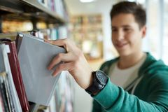 Close up of happy student boy with book in library Stock Photo