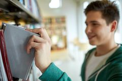 Close up of happy student boy with book in library Royalty Free Stock Images