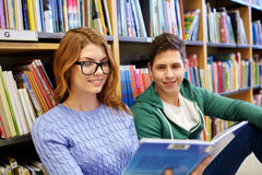 Close up of happy students reading book in library Stock Photos
