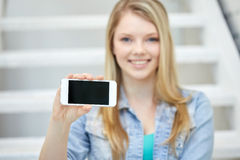 Close up of happy teenage girl showing smartphone Royalty Free Stock Image