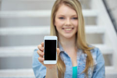 Close up of happy teenage girl showing smartphone Stock Image