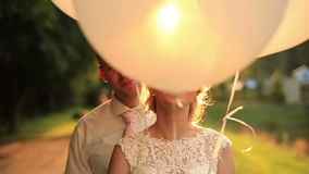Close up of happy wedding couple hiding face by the balloons and having fun in the autumn park on sunset.  stock video footage