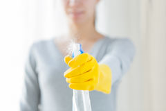 Close up of happy woman with cleanser spraying. People, housework and housekeeping concept - close up of happy woman with cleanser spraying home Stock Photography
