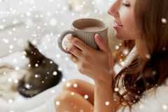 Close up of happy woman with cup of cocoa at home. Winter, cosiness, leisure and people concept - close up of happy young woman with cup of coffee or cacao and stock photo