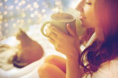 Close up of happy woman with cup of cocoa at home. Winter, cosiness, leisure and people concept - close up of happy young woman with cup of coffee or cacao and stock images