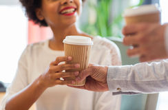 Close up of happy woman hand taking coffee cup. People, drinks and care concept - close up of happy african american women hand taking coffee cup from man Stock Photography