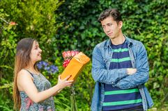 Close up of happy woman holding a gift and flowers looking at his crush and boy with his arms crossed and looking at her. Close up of happy women holding a gift Stock Images